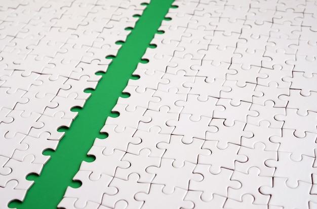 El camino verde se coloca en la plataforma de un rompecabezas plegado blanco