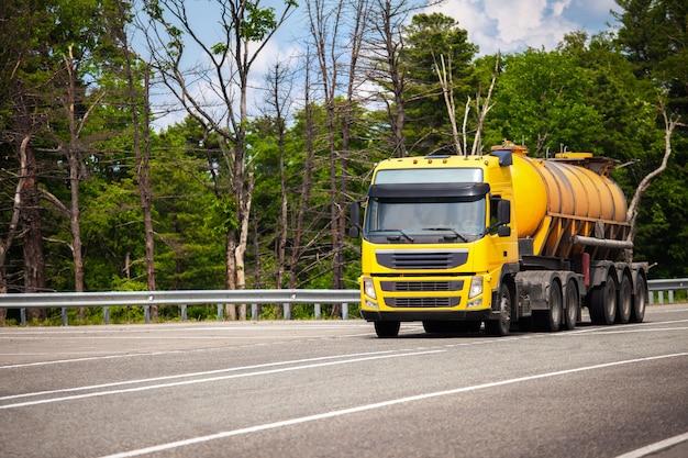 Camión amarillo con semirremolque tanque naranja en una carretera