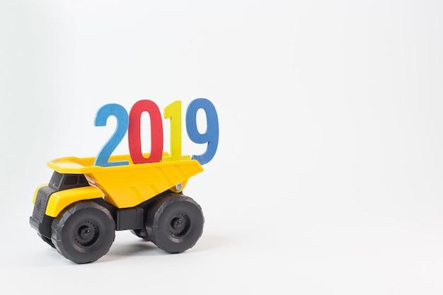 El camión amarillo tiene número 2019 sobre fondo blanco.