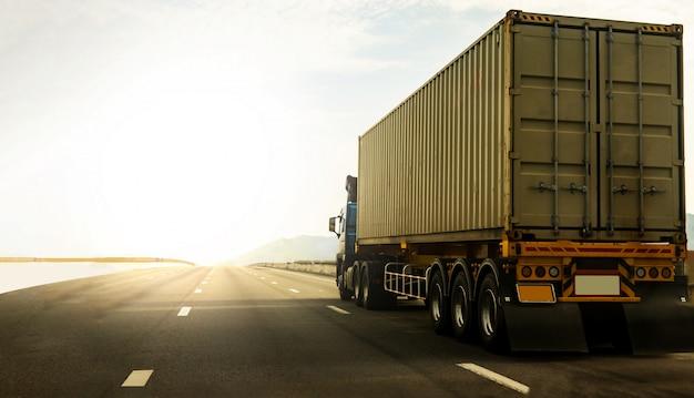 Camión de carga en carretera con contenedor, concepto de transporte, importación, exportación, logística, transporte industrial, transporte terrestre en la autopista contra el cielo del amanecer