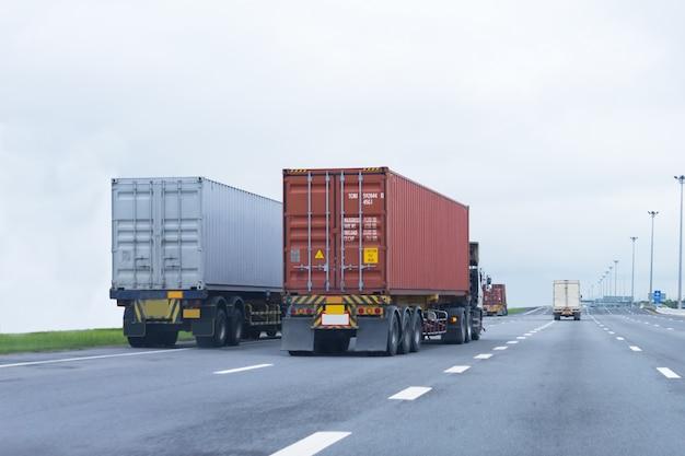 Camión en carretera con contenedor rojo, importación, exportación logística industrial.