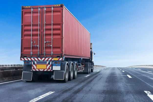 Camión en la carretera con contenedor rojo, transporte logístico en la autopista de asfalto