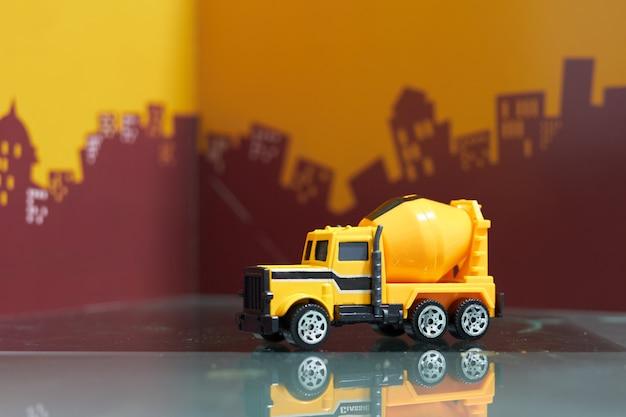 Camión de cemento amarillo en la ciudad borrosa
