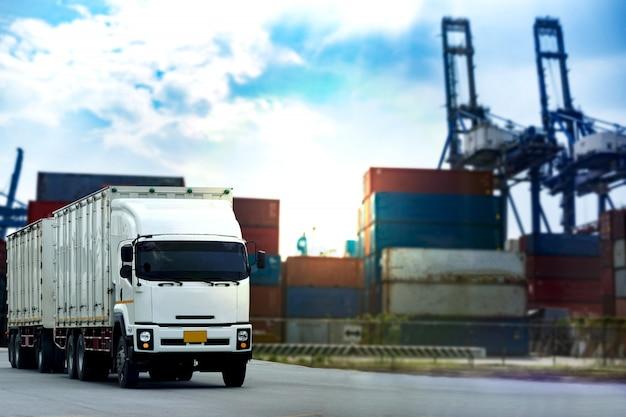 Camión contenedor de carga blanca en el puerto de barcos logística