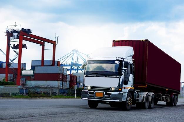 Camión de contenedores de carga roja en el puerto de buques logística