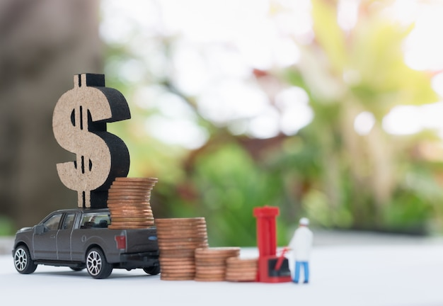 Camión miniatura con signo de dólar con pila de monedas