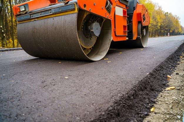 Camión de pavimento industrial. colocación de asfalto fresco en el sitio de construcción. industria de maquinaria pesada. ingeniería mecánica.