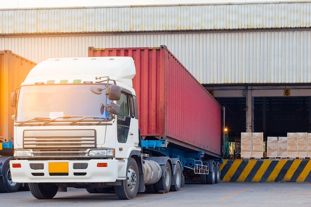 El camión de remolque de contenedores de carga de embarque en el almacén, logística de la industria de carga y transporte