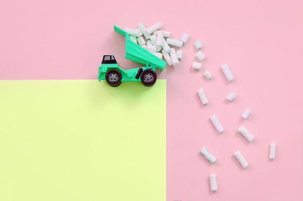El camión volquete arroja piezas de malvavisco desde su espalda levantada