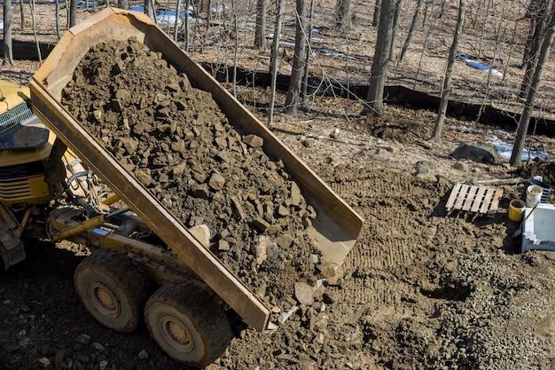 Un camión volquete articulado de vía grande descarga de roca y suelo en una nueva carretera en proyecto de construcción