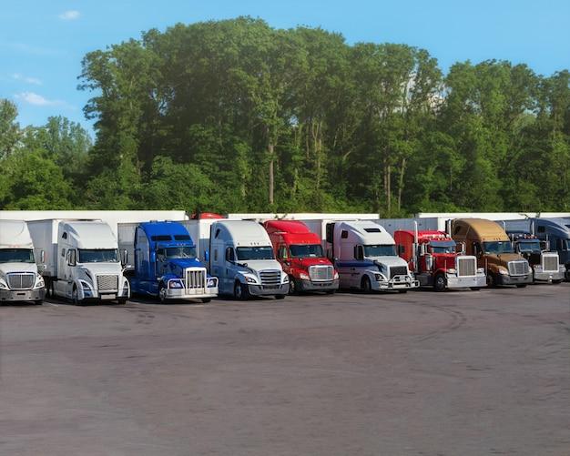 Los camiones modernos de varios colores y modelos de transporte de diferentes tipos de productos comerciales se colocan en fila en el estacionamiento de la parada de camiones para que el conductor del camión descanse según el libro de registro.