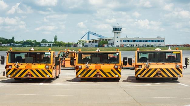 Camiones naranjas para el transporte de equipaje.