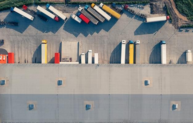 Los camiones con remolques se cargan y descargan en la terminal de carga en la mañana superior vu airive shot ...