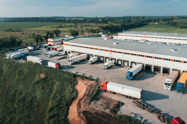 Los camiones con remolques se cargan y descargan en la terminal de carga en la toma aérea de la mañana contai ...
