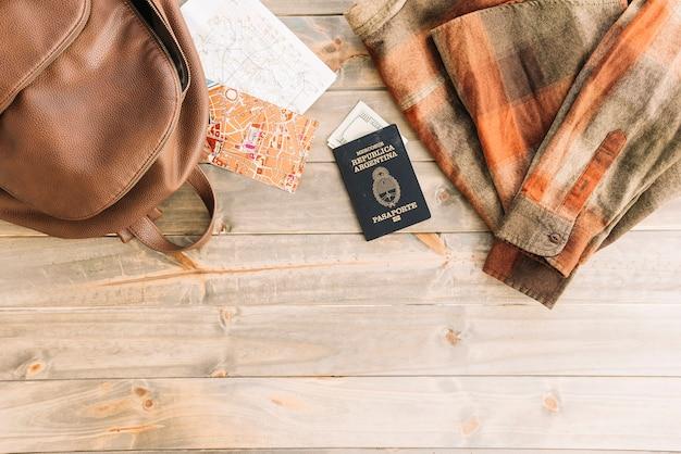 Camisa a cuadros; bolso; mapa; pasaporte y moneda sobre fondo de madera.