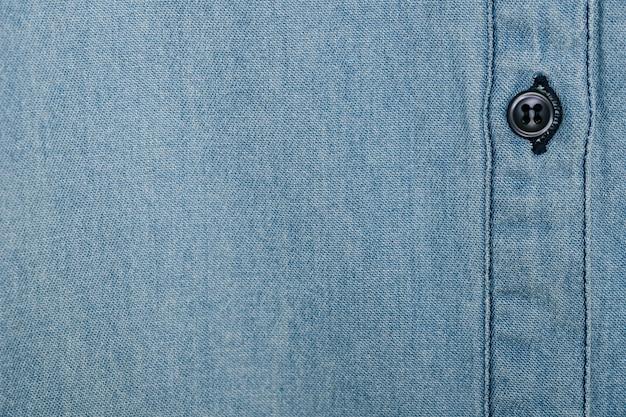 Camisa denim azul claro con botón negro.