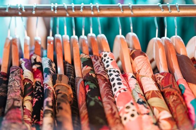 Camisa floral en la percha que cuelga en el carril en la tienda de ropa