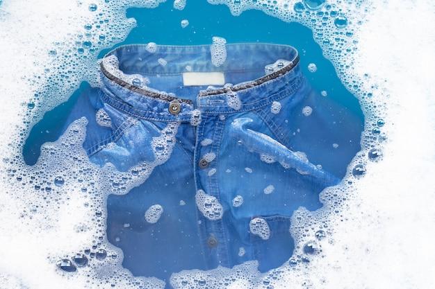 Camisa de jean remojar en detergente en polvo de disolución de agua. concepto de lavandería