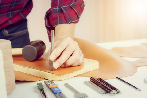 Camisa roja de cuero, artesano que trabaja con herramientas artesanales, perforaciones de cordones, costura en cuero genuino.