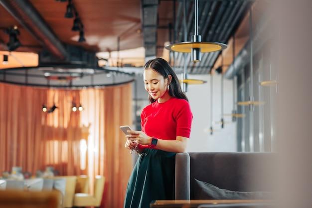 Camisa roja elegante mujer de pelo oscuro con camisa roja y reloj inteligente rojo de pie junto a la mesa