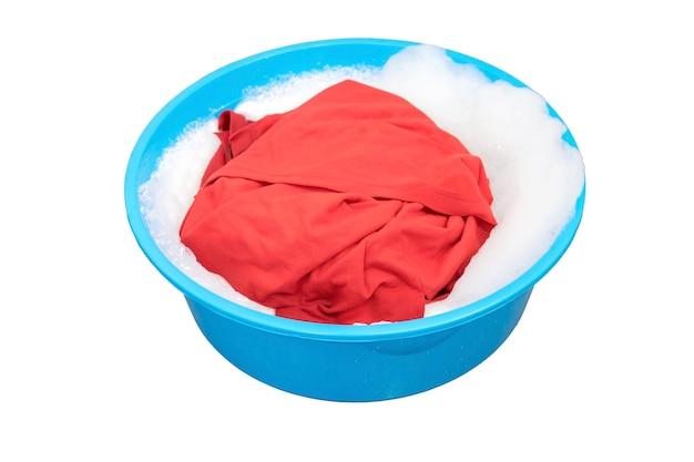 Camisa roja empapada en detergente en el recipiente de plástico