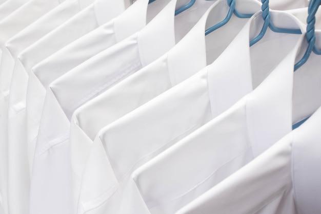 Camisas blancas colgando en estante en una fila