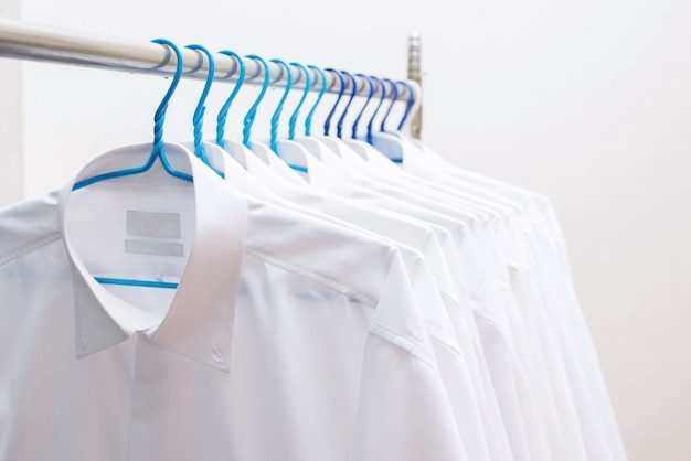Camisas blancas que cuelgan en la rejilla en una fila