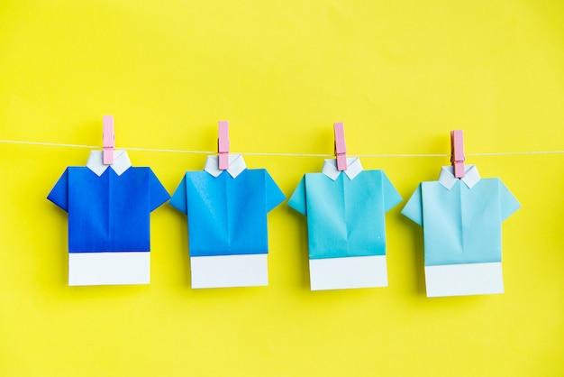 Camisas de papel dobladas que cuelgan en la línea de ropa