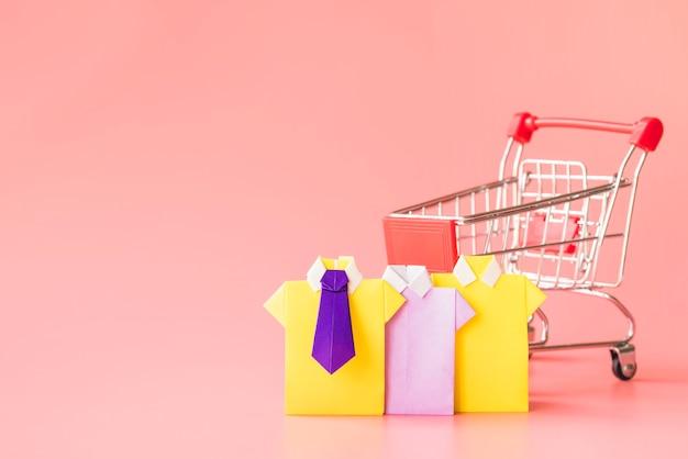 Camisas de papel de juguete de colores cerca de carrito de compras