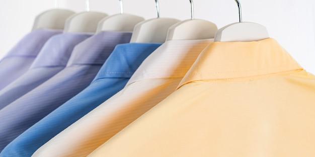 Camisas de vestir para hombres, ropa en perchas sobre fondo blanco.
