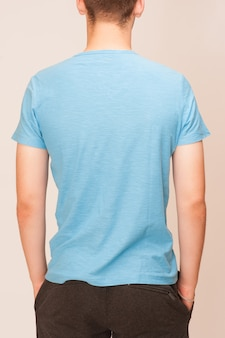 Camiseta azul sobre un joven aislado, espalda.