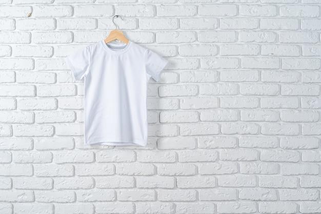 Camiseta blanca colgada en la percha contra la pared de ladrillo, espacio de copia