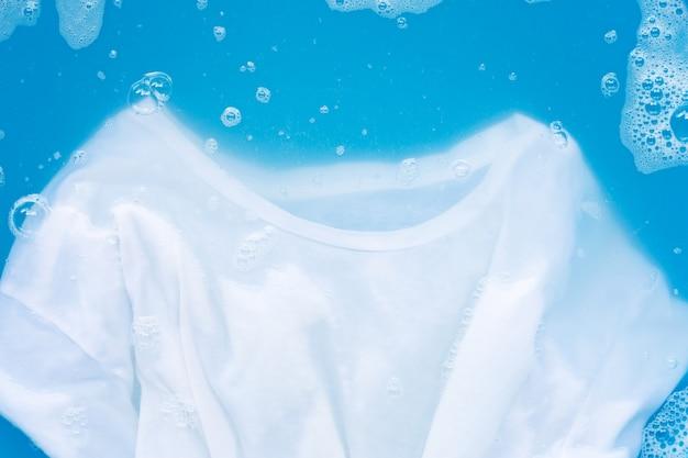 Camiseta blanca empapada en detergente en polvo disolución de agua, paño de lavado.
