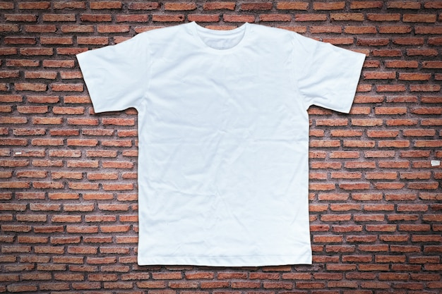 Camiseta blanca sobre fondo de pared de ladrillo.