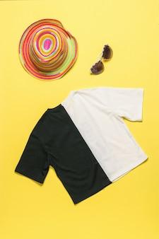 Camiseta en blanco y negro, sombrero multicolor y gafas sobre una superficie amarilla