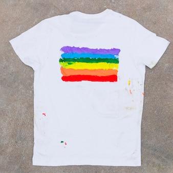 Camiseta con el emblema del arcoiris sobre asfalto.