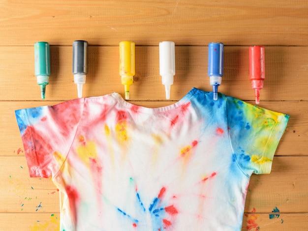 Camiseta estilo tie dye y seis latas de pintura de tela en la mesa de madera.