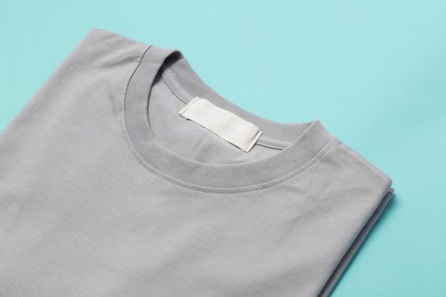 Camiseta gris doblada con etiqueta en blanco para su diseño aislado
