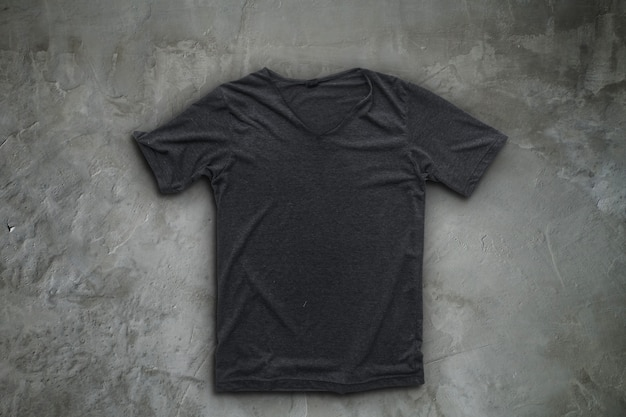 Camiseta gris sobre fondo de muro de hormigón.