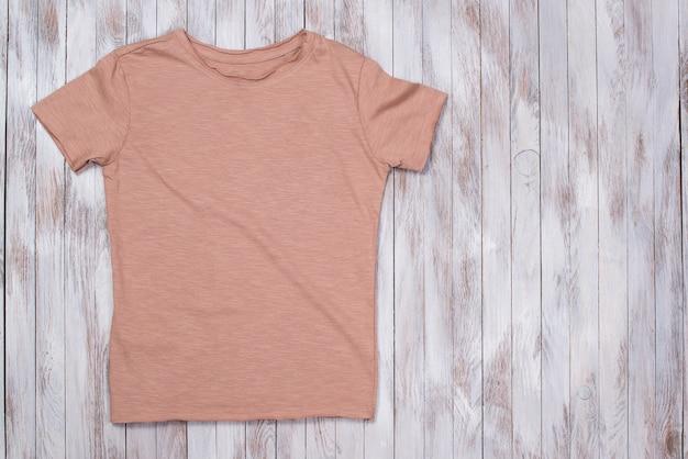 Camiseta de pintura de color con espacio de copia. maqueta de camiseta, endecha plana. mesa de madera con estilo.