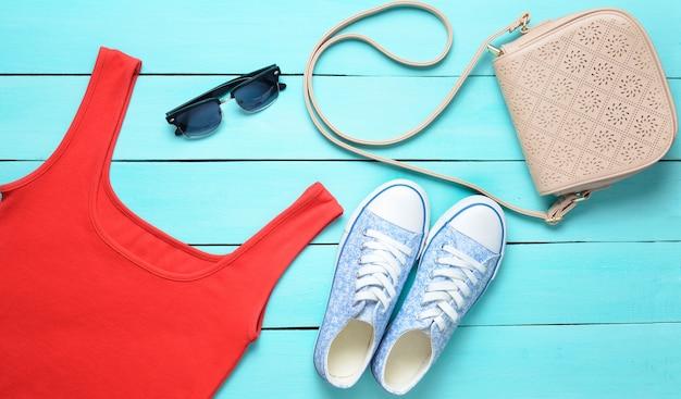 Camiseta roja, zapatillas de deporte, bolso de cuero, gafas de sol en una mesa de madera azul.