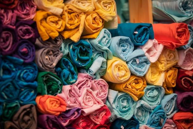 Camiseta de rollo abstracto de colorsful detalle de primer plano de la textura de la tela multicolor en el estante.