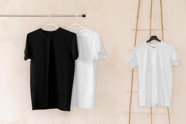 Camisetas blancas y negras en perchas para presentación de diseño, espacio de copia