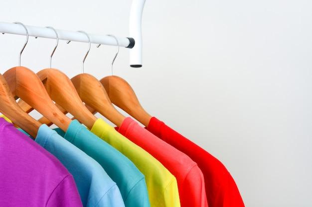 Camisetas coloridas del arco iris colgando en una percha de madera sobre fondo blanco