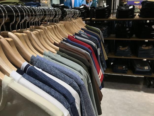 Camisetas que cuelgan en un estante para la venta.