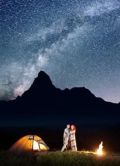 Campamento brilla por la noche bajo las estrellas.