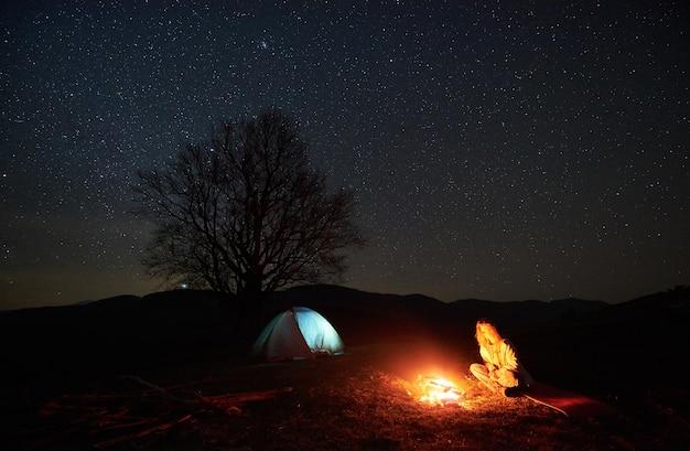 Campamento nocturno. caminante descansando junto a la fogata bajo el cielo estrellado