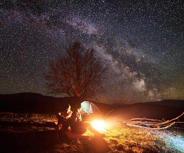 Campamento nocturno. excursionistas descansando cerca de la fogata bajo el cielo estrellado.