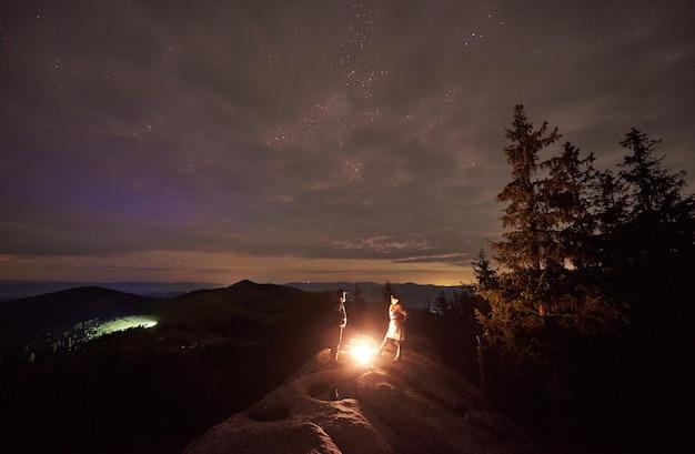 Campamento nocturno con gente alrededor de una fogata bajo el cielo estrellado de la noche.