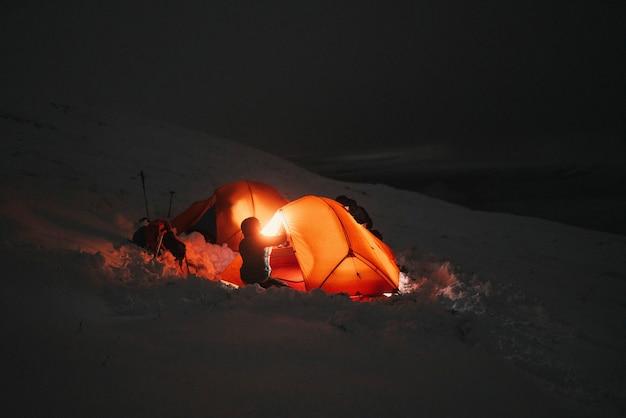 Campamento nocturno en una montaña nevada.